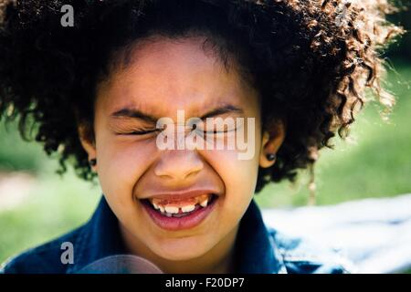 Close up portrait of girl with eyes closed pulling face - Stock Photo
