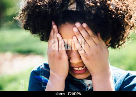 Close up portrait of girl covering face with hands - Stock Photo