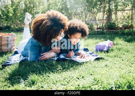 Mother and daughter lying on fronts, side by side, reading book together - Stock Photo