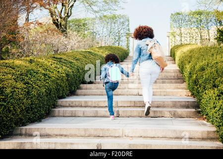 Rear view of mother and daughter holding hands going up stairway - Stock Photo