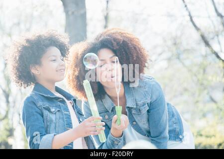 Mother and daughter blowing bubbles together - Stock Photo