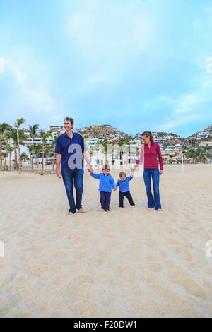 Young family, walking on beach, holding hands - Stock Photo