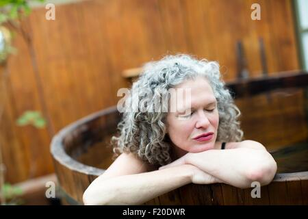 Mature woman resting on hands in hot tub at eco retreat - Stock Photo
