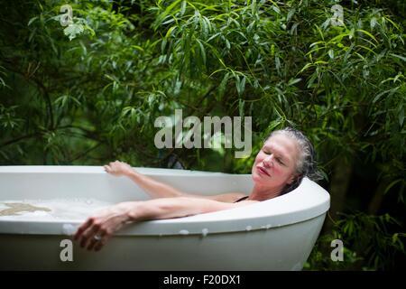 Mature woman relaxing in garden bubble bath at  eco retreat - Stock Photo