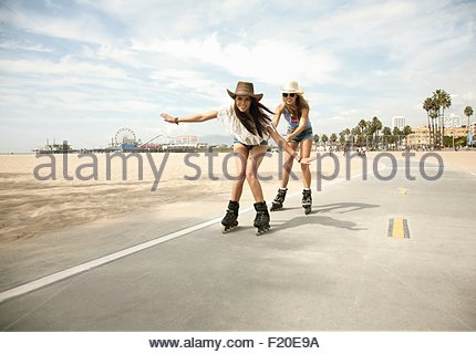 Portrait of two young women, inline skating - Stock Photo
