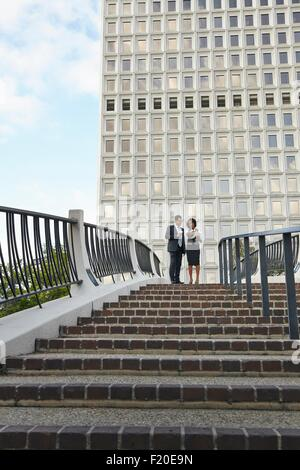 Low angle view of business people standing at top of stairway, City Hall East, Los Angeles, California, USA - Stock Photo
