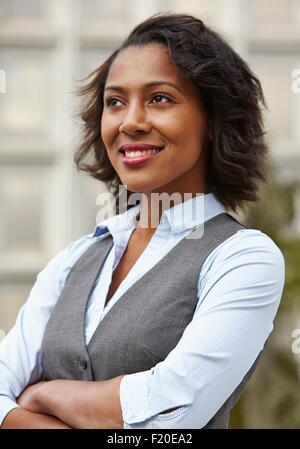 Portrait of young business woman, wearing waistcoat, looking away, arms folded, smiling - Stock Photo