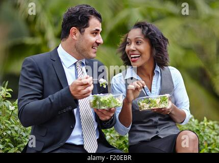 Business people sitting side by side enjoying a salad on lunch break, face to face, smiling - Stock Photo