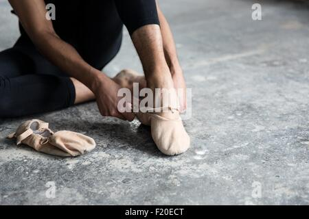 Dancer wearing ballet shoe in studio - Stock Photo