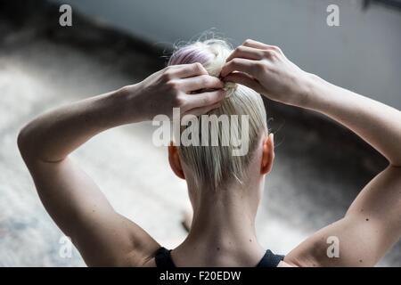 Woman tying up hair in studio - Stock Photo