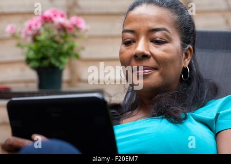 Mature woman sitting in garden reading digital tablet - Stock Photo
