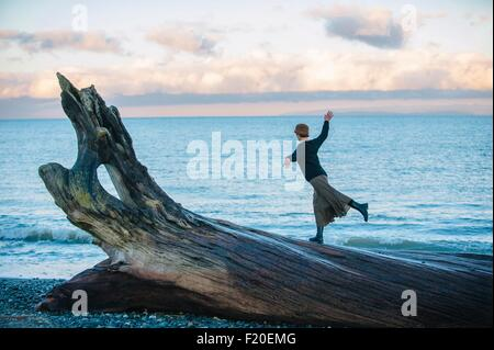 Woman standing on large driftwood tree trunk on beach - Stock Photo