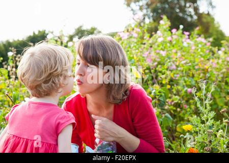 Mid adult mother and toddler daughter kissing in flower field - Stock Photo