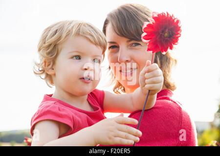 Portrait of mid adult mother and toddler daughter holding red flower in field - Stock Photo