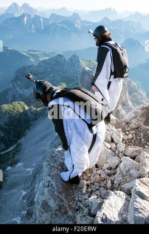 Two male BASE jumpers preparing to launch from mountain, Dolomites, Italy - Stock Photo