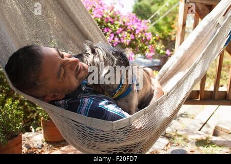 Mid adult man reclining in garden hammock with dog - Stock Photo