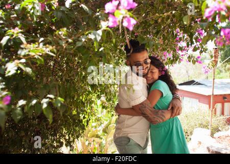 Mid adult man hugging daughter in garden - Stock Photo