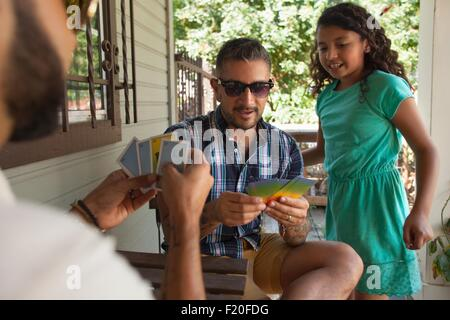 Girl watching father and his brother play cards in porch - Stock Photo
