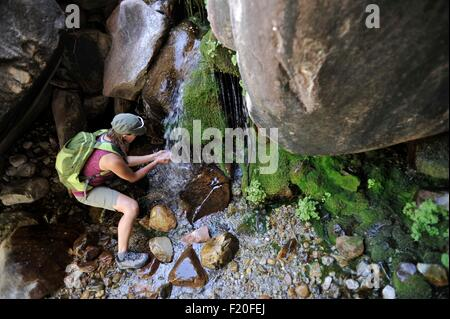High angle view of hiker cupping hands under waterfall collecting water - Stock Photo
