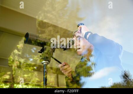 Senior man at home, using telescope through window - Stock Photo