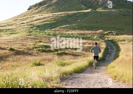 Rear view of young male runner running up hillside track - Stock Photo