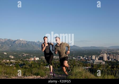 Young female and male runners racing along track above city in valley - Stock Photo