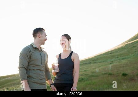 Young female and male runner taking a water break on hillside - Stock Photo