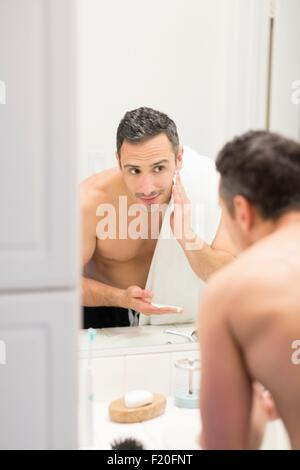 Mid adult man, looking in mirror, applying shaving foam to face, rear view - Stock Photo