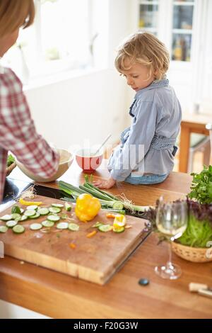 Mother and son preparing meal in kitchen - Stock Photo
