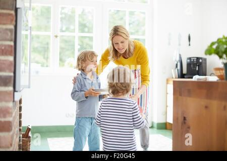 Boys giving helping hand to mother in kitchen - Stock Photo