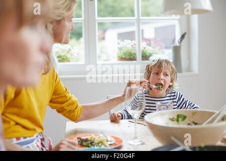 Mother feeding son at dining table - Stock Photo