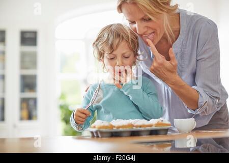 Mother and son making cupcakes in kitchen - Stock Photo
