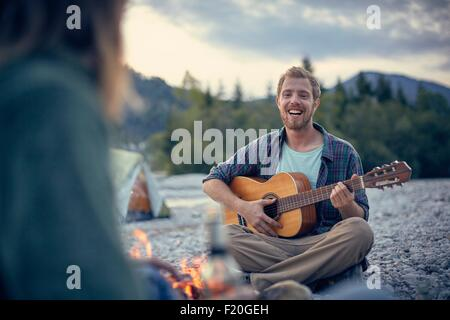Front view of young man sitting by campfire playing guitar - Stock Photo
