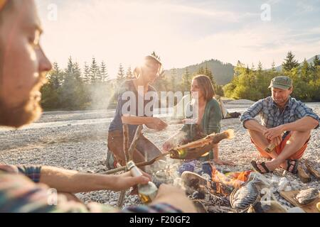 Adults sitting around campfire cooking fish - Stock Photo
