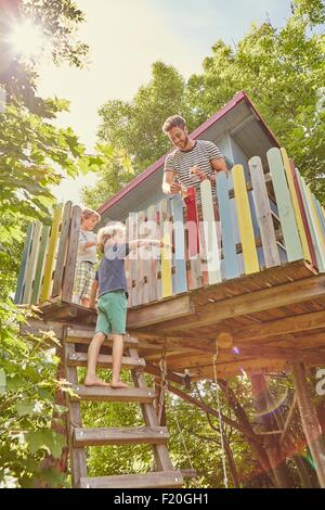 Father and two sons, painting tree house - Stock Photo