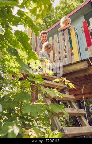 Father and two sons, painting tree house, low angle view - Stock Photo
