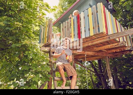 Portrait of father and two sons painting tree house - Stock Photo
