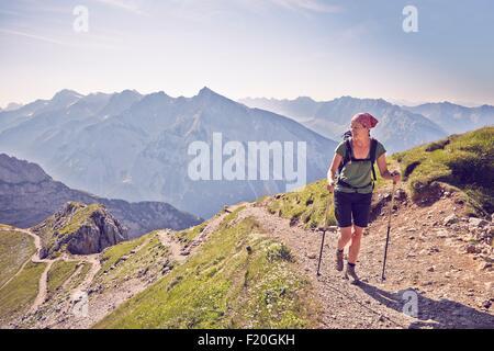 Mature woman hiking along mountain path, Karwendel-Mittenwald, Bavaria, Germany - Stock Photo