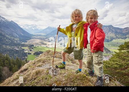 Portrait of two young boys, standing on hilltop, Garmisch-Partenkirchen, Bavaria, Germany - Stock Photo