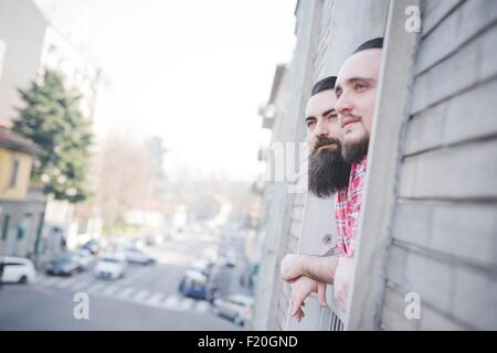 Gay couple looking out of window - Stock Photo