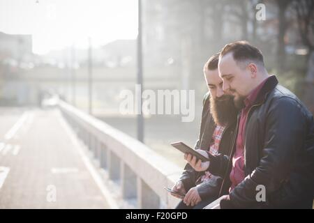 Gay couple using smartphone on pavement - Stock Photo