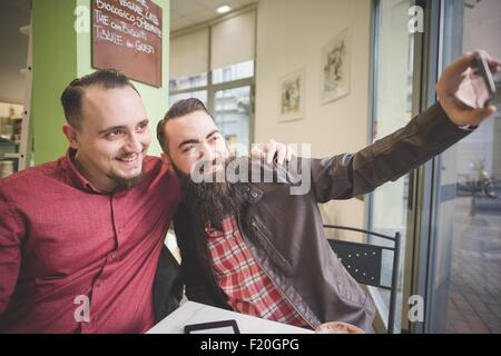 Gay couple taking selfie in cafe - Stock Photo