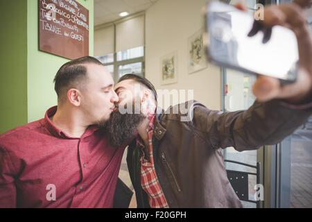 Gay couple taking selfie and kissing in cafe - Stock Photo