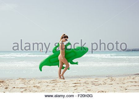 Young woman wearing bikini carrying inflatable crocodile on beach - Stock Photo