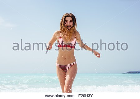 Portrait of young woman wearing bikini running in sea - Stock Photo