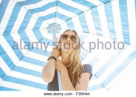 Low angle portrait of young woman holding up striped beach umbrella - Stock Photo
