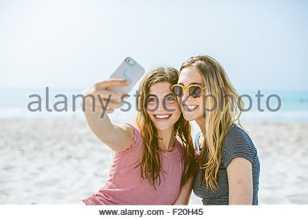 Two young female friends taking smartphone selfie on beach - Stock Photo