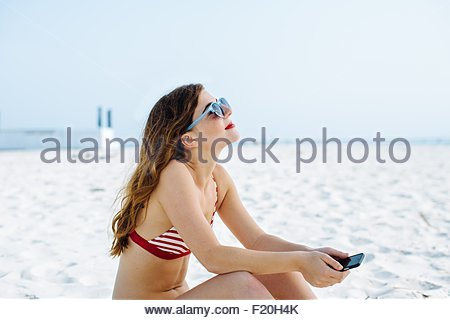 Young woman wearing bikini top and sunglasses sitting on beach with smartphone - Stock Photo