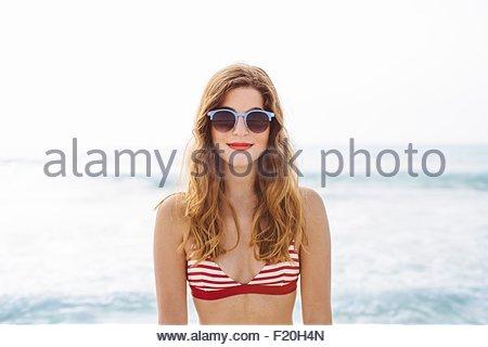 Portrait of young woman wearing bikini and sunglasses at coast - Stock Photo