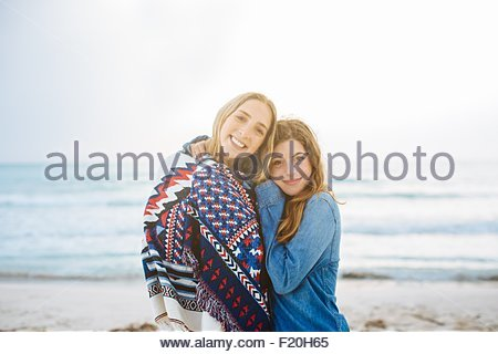 Portrait of two young female friends hugging on beach - Stock Photo